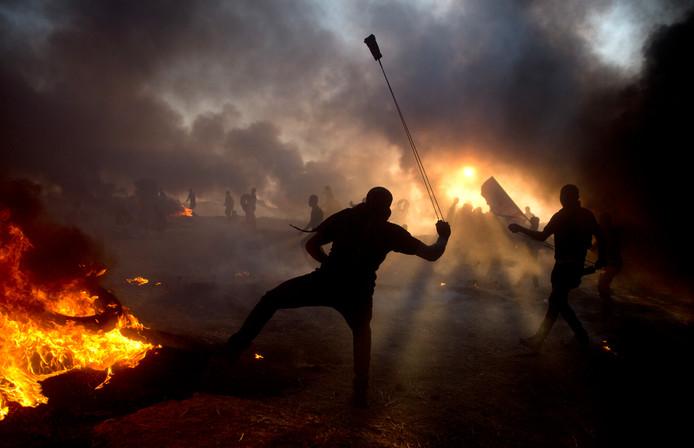 Tussen brandende autobanden en terwijl Israëlische troepen reageren met traangas, gooien de demonstranten stenen naar de Israëlische soldaten.
