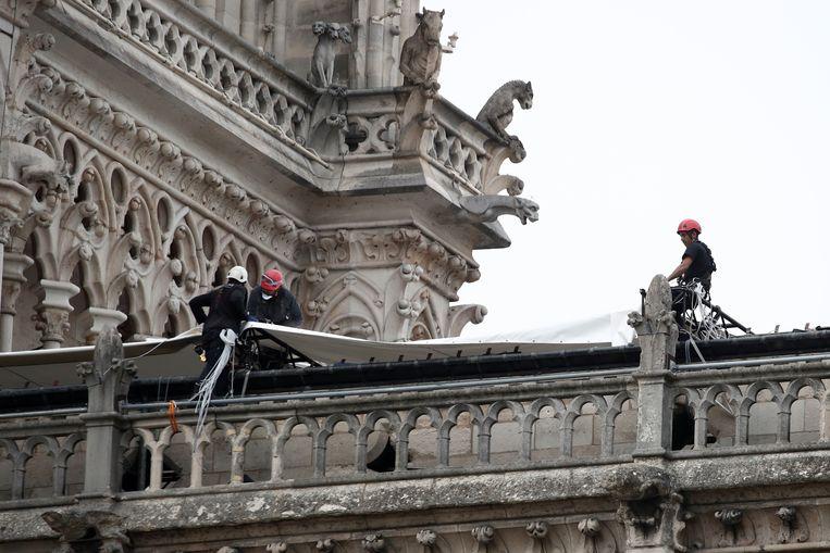 Boven het vernielde dak hebben enkele arbeiders een groot dekzeil aangebracht. Zo moet de kathedraal beschermd worden tegen de aangekondigde regen.