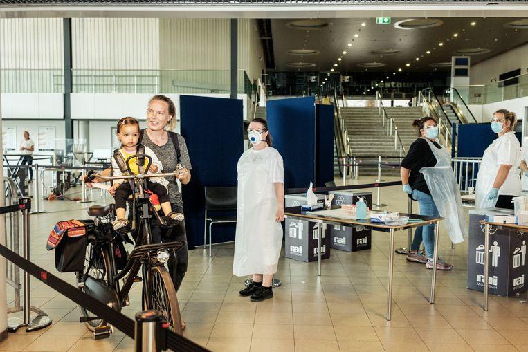 Sanne Tames en haar dochter Ella laten zich testen in de RAI. Beeld Jakob van Vliet
