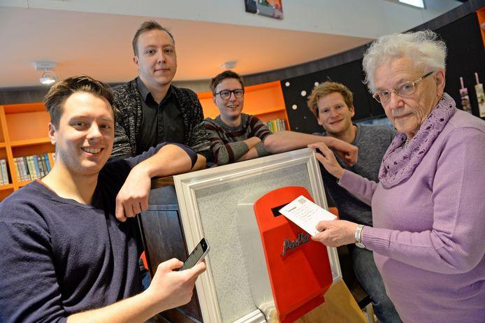 Oma Wolf gooit haar eerste kaartje in de digitale brievenbus die Wessel Fletterman (r.) op zijn smartphone als app ontvangt. In het midden de drie medeontwikkelaars Joran van der Sluis, Mark Zwart en Folkert Prins.