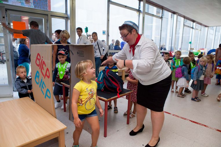 Juf Delphine leidt de kinderen naar hun juiste gate.