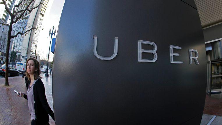 Een vrouw loopt voorbij het logo van Uber in San Francisco. Beeld AP
