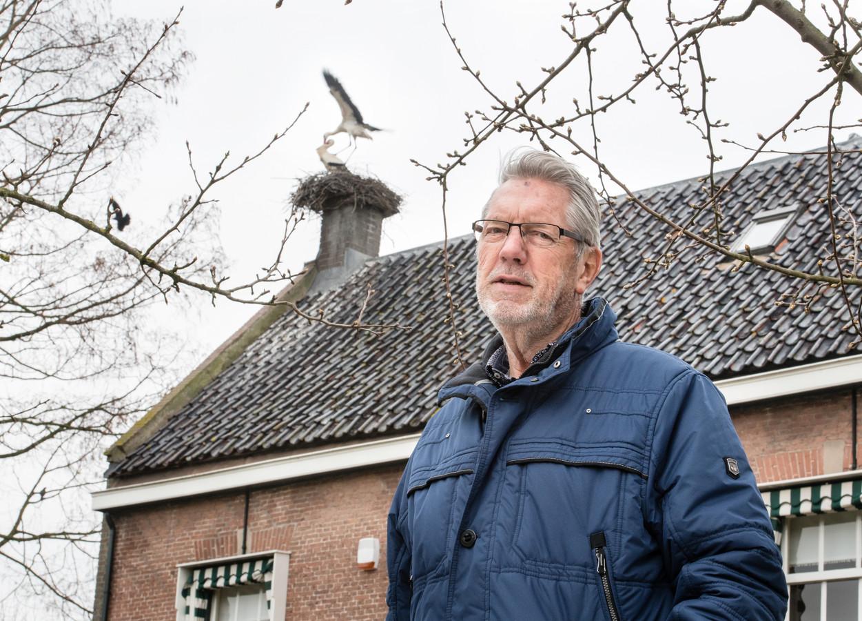 Kees Vos voor zijn woonboerderij in Herwijnen met een van de drie ooievaarsnesten op het dak.