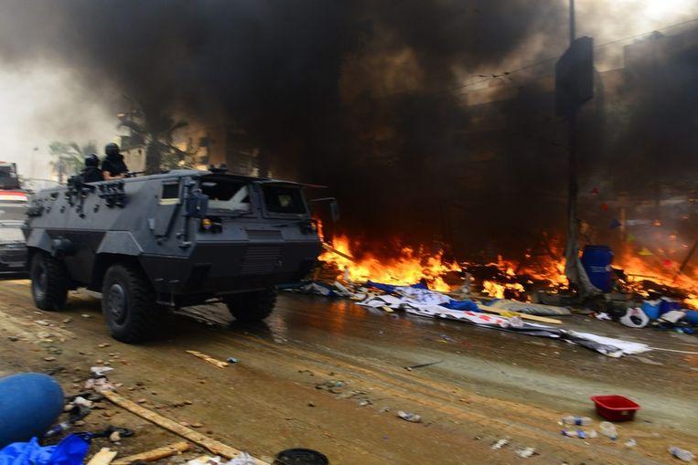 Een legervoertuig bij de brandende reste van een tentenkamp. Beeld epa