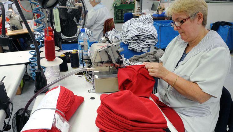 Rode mutsen in een Franse textielfabriek. Beeld afp