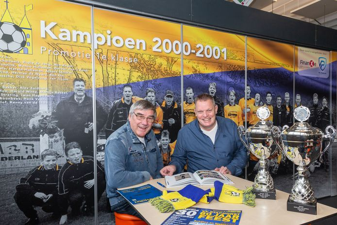 Jan Vogelzang en Bennie Miggels bladerend door een oud-jubileumboek. Belangrijke trofeeën uit de clubhistorie pronken op tafel, op de fotowand prijkt het kampioenselftal.