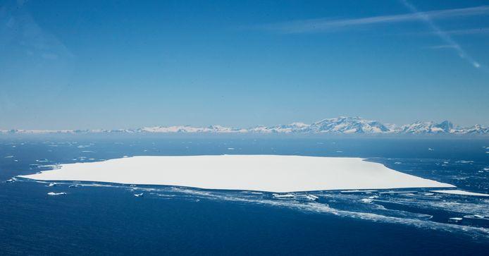 Vooraan in beeld ijsberg A-68D, die afbrak van het noordelijke deel van 'moederberg' A68A. In de achtergrond het eiland South Georgia.
