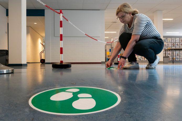 Mirjam Hattink, hoofd facilitair bij het Ds. Pierson College in Den Bosch plakt vriendelijke voetstappen op de vloer. ,,Bij elk lokaal hebben we moeten kijken hoe we de tien tafels neer konden zetten.''