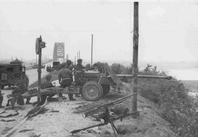 Het Britse antitankkanon (Quick-firing 17 pounder) staat kort na de verovering van de Waalbrug opgesteld, wijzend richting de Duitse dreiging vanuit de Ooij.