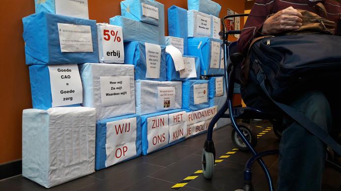Bij de ingang van het Beatrixziekenhuis staat leuzen verdeeld over dozen, symbolisch de bouwstenen van zorg.