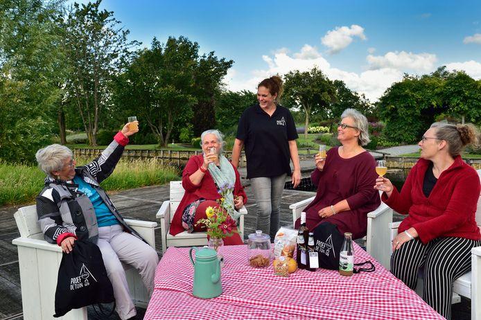 Bezoekers Marion van den Eijnden, Marike van IJssel, Saskia Beentjes en Thera Rooth (v.l.n.r., zittend aan tafel) genieten van een borrelpicknick op de Proeftuin van Holland. Ze eten hapjes en drankjes uit de borreltas van Proeftuin-uitbaatster Desiree Niesing (m).