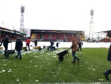 Supporters GA Eagles halen duizenden kruiwagens sneeuw van het veld