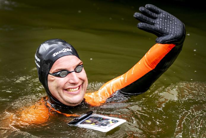 Olympisch zwemkampioen Maarten van der Weijden bij het 'stempelpunt' in Sloten op de eerste dag van zijn 11stedenzwemtocht.