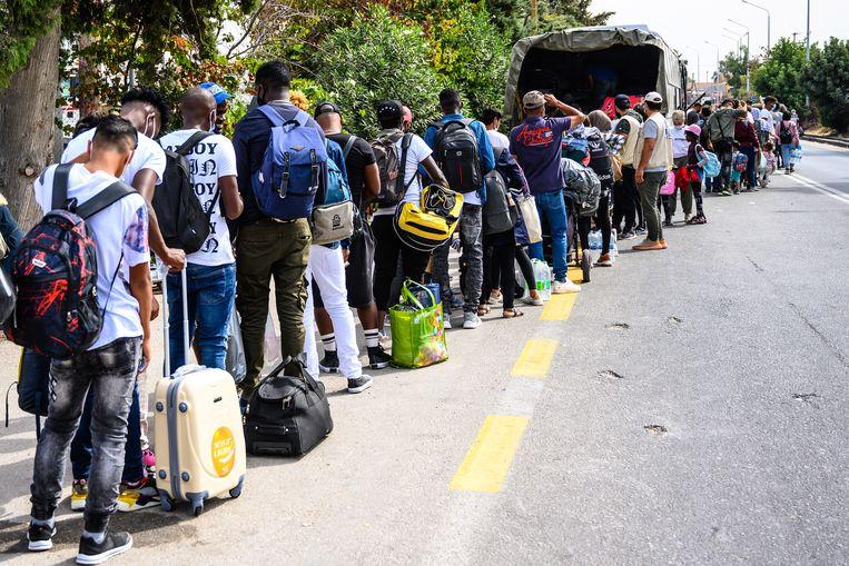 Vluchtelingen en migranten wachten tot ze in een bus kunnen stappen bij het kamp Kara Tepe naar de haven van Mytilene op Lesbos.  Van daaruit gaan ze naar het Griekse vasteland en dan eventueel verder naar een andere Europese bestemming.  Beeld Vangelis Papantonis / EPA
