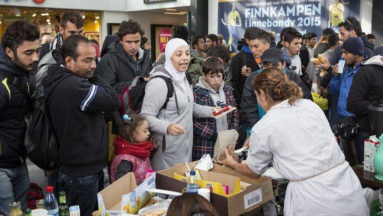 Vluchtelingen die aankomen op het station van het Zweedse Malmö krijgen eten. Beeld EPA