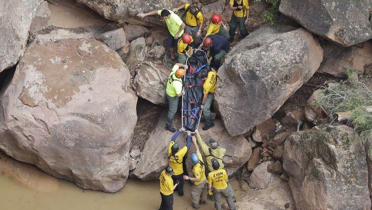 Reddingswerkers zijn bezig de lichamen te bergen van de slachtoffers. Beeld ap