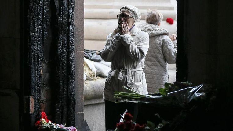 Een vrouw staat voor de ingang van het afgebrande vakbondsgebouw in Odessa. Meer dan veertig mensen kwamen om het leven.
