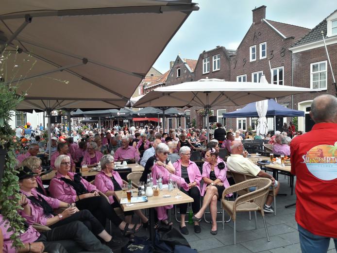 Leden van Suuk7 luisteren naar het collegakoor uit Sint Anthonis: de Traonentrekkers op de Markt in Gennep.