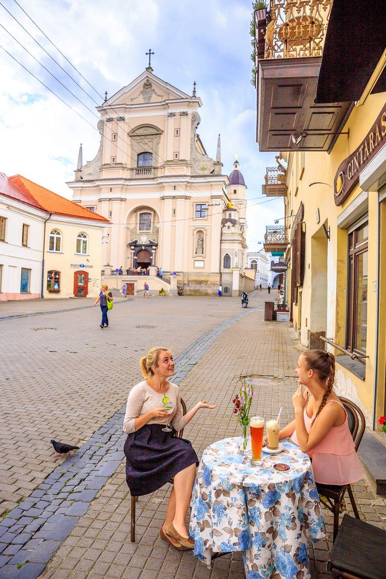 IJskoffie, gin-tonic en weizen drinken voor de Sint Theresakerk in Vilnius. Beeld Ruben Drenth