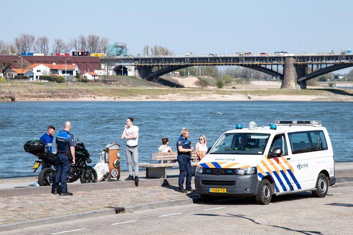 Handhavers zijn druk op de Waalkade met het aanspreken van mensen. De mensen op de foto zijn niet bekeurd.