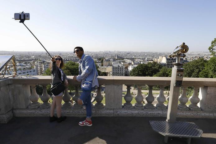 Toeristen nemen een foto van zichzelf met een selfiestick in Montmartre, Parijs.