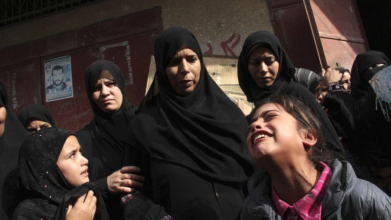 Familieleden huilen bij de begrafenis van een man en zijn dochter, die bij een luchtaanval zijn omgekomen. Beeld ap
