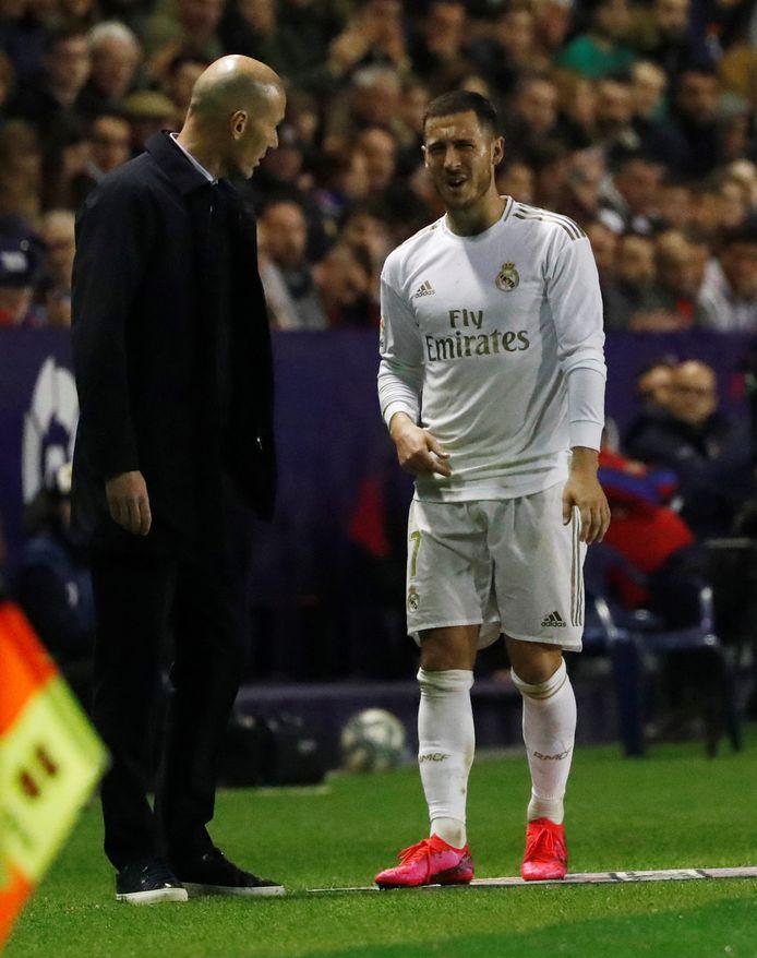 De geblesseerde Hazard in gesprek met zijn coach Zinedine Zidane.