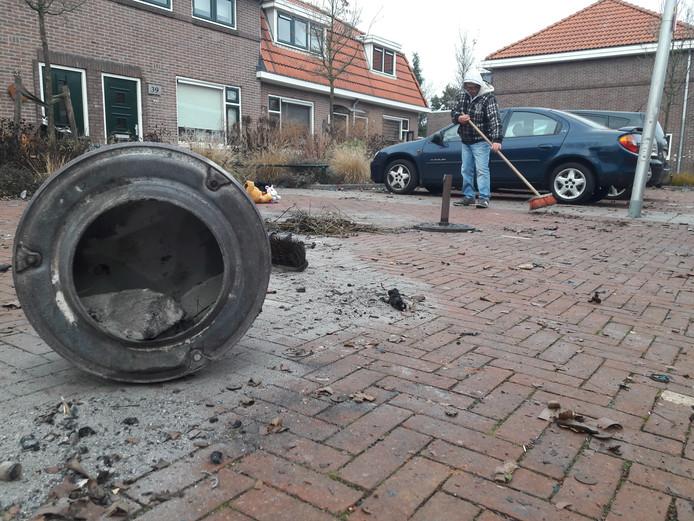 Een buurman veegt de plek schoon, waar Henk Kempers uit Enschede vlak na middernacht als gevolg van een vuurwerkexplosie overleed.