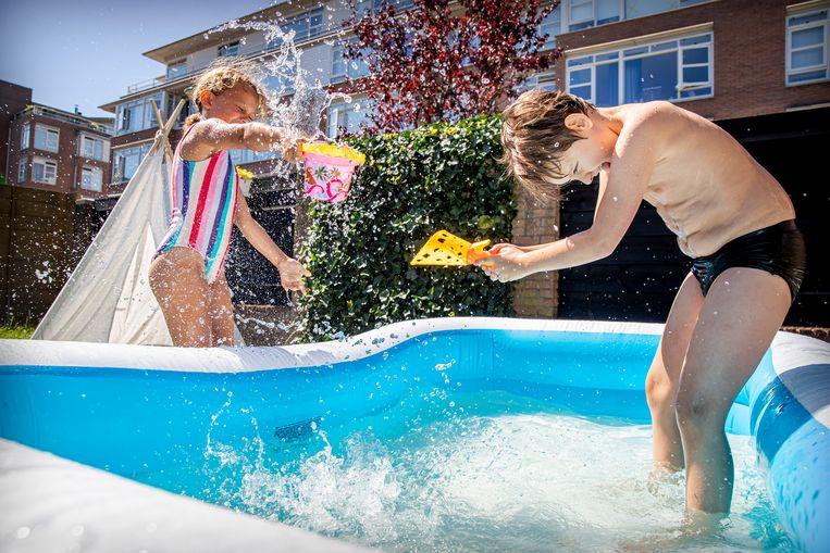 Kinderen spelen in een zwembadje in de tuin. Vitens vraagt klanten om geen badjes meer te vullen. Beeld BSR Agency