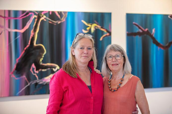 Elise Huijberts (links)  en Jantina Boelens voor het lievelingswerk van de curator, de doeken van kunstenares Justyna Pennards.