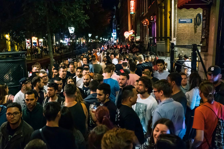 Enorme drukte op de Oudezijds Achterburgwal in Amsterdam, zaterdagavond. Voor politie en hulpverleners is er geen doorkomen aan.