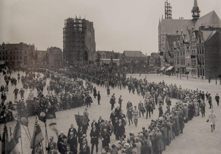 Terwijl op de achtergrond de vernielde Lakenhalle worden heropgebouwd, marcheert een stoet door Ieper. Dat telt op 1 maart 1919 nog welgeteld 125 inwoners.