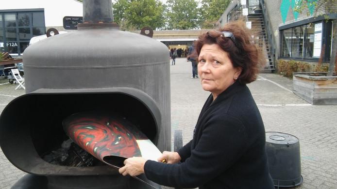 Jolande Otten van Onterfd Goed stopt op Sectie C het eerste schilderij in de grote kachel waarin een dertigtal doeken zijn verbrand.