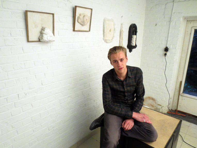 Kunstenaar Simon Verheylesonne in zijn nieuwe atelier met enkele van zijn wekren aan de muur.