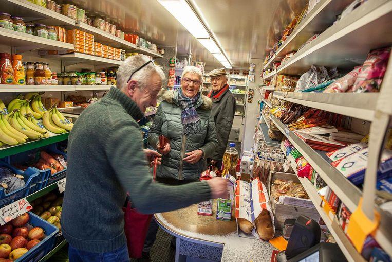 Adolf Schaap helpt in zijn rijdende winkel inwoners van Ulrum aan de dagelijkse boodschappen. Beeld null