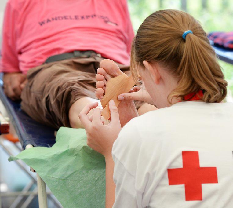 Een vrijwilliger van het Rode Kruis verzorgd blaren van een wandelaar van de Nijmeegse Vierdaagse. Beeld anp