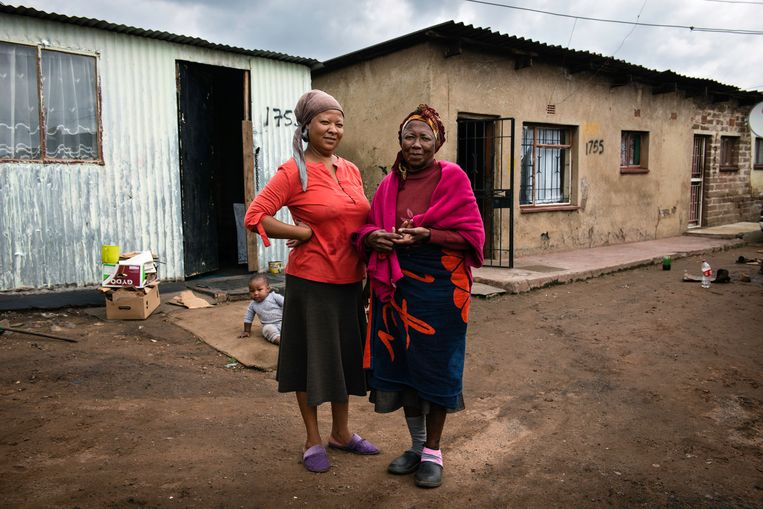 Doris Harrison (links) en haar 69-jarige moeder voor hun woning in sloppenwijk Freedom Charter in het Zuid-Afrikaanse township Soweto.  Beeld Bram Lammers
