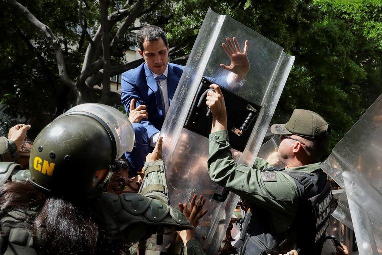 Oppositieleider Juan Guaidó probeert over een hek te klimmen om het parlementsgebouw binnen te komen. Beeld EPA