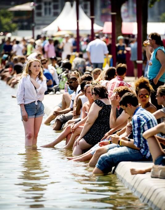 Mensen zoeken verkoeling in het water van de vijver op het Museumplein.