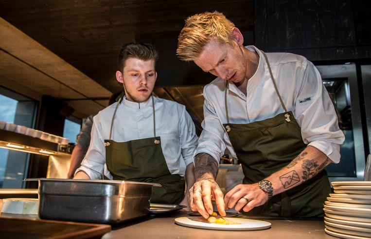 Alex Verhoeven (rechts) dresseert een bord in zijn nieuwe restaurant Hert