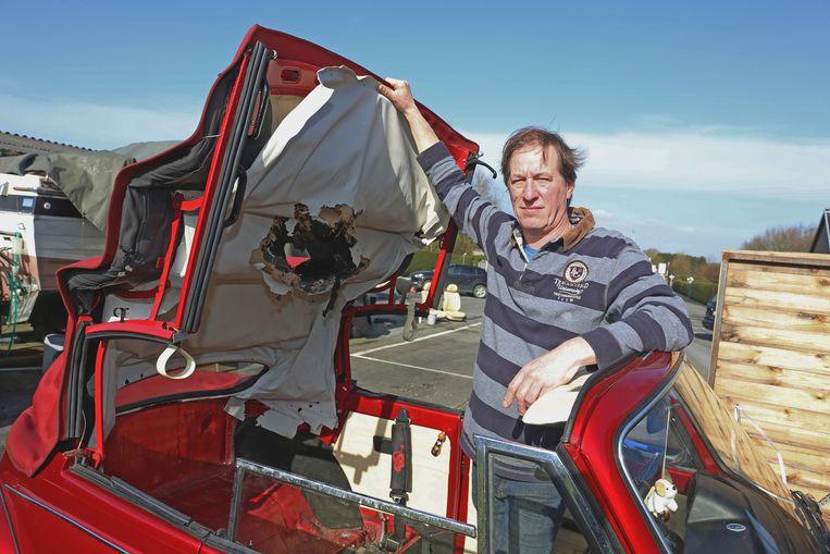 Dirk Van Sinay bij de vernielde wagen. De dieren beten een groot een gat in het dak.