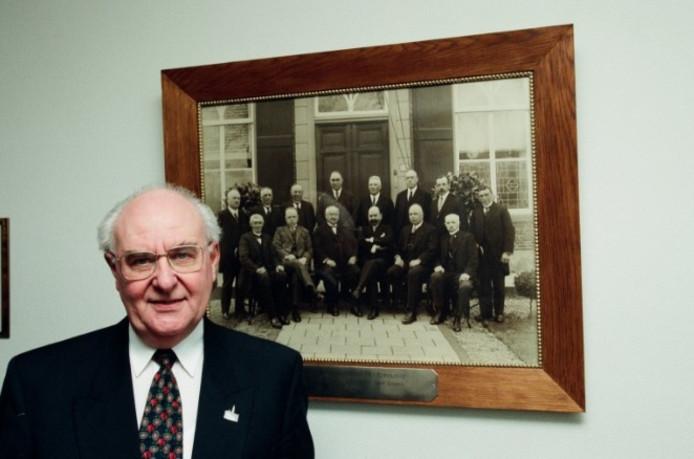 Portret van Arnold van den Berg, scheidend burgemeester Teteringen, eind 1996.  Op de achtergrond een foto van het Teteringse gemeentebestuur van 1927, kort voor de eerste (gedeeltelijke) annexatie door Breda