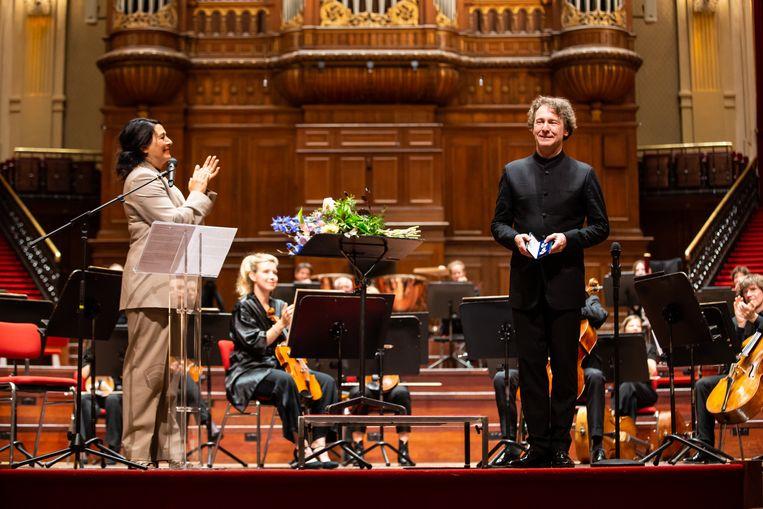 Bij zijn afscheid als chef-dirigent van het Nederlands Philharmonisch Orkest kreeg de verraste Marc Albrecht zaterdag een koninklijke onderscheiding uit handen van de Amsterdamse wethouder voor cultuur Touria Meliani. Beeld Melle Meivogel