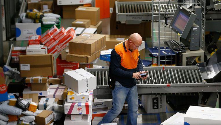 Bezorgbedrijven draaien overuren om de hoeveelheid bestelde pakketjes op tijd te bezorgen. Beeld null