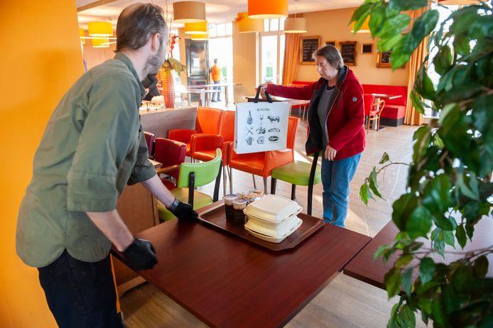 Kok Roy van Wijk zet, met gepaste afstand, de maaltijd voor een klant op tafel.