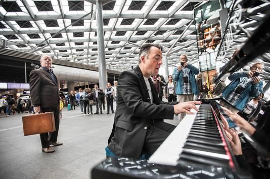 De Zwolse stationspianist Hans Jansen op station Den Haag CS tijdens zijn recordpoging om alle stationspiano's in Nederland te bespelen.