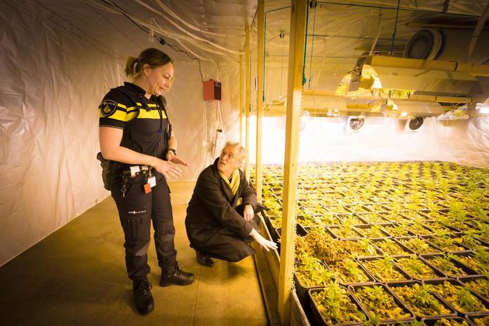 Politieagent Esther Janssen praat burgemeester John Jorritsma van Eindhoven bij over de aangetroffen hennepfabriek.