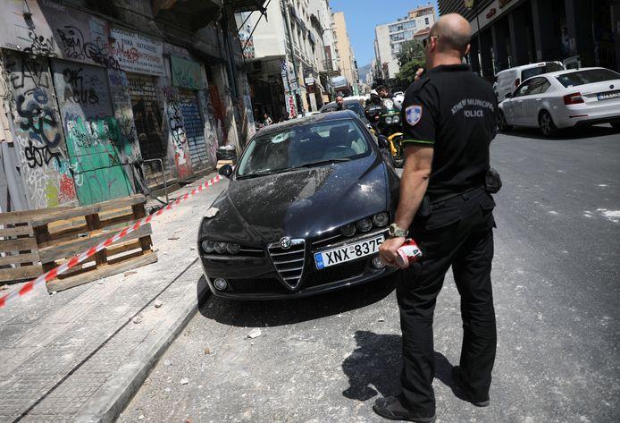 Een politieagent bij een auto die beschadigd raakte door neerkomend puin.