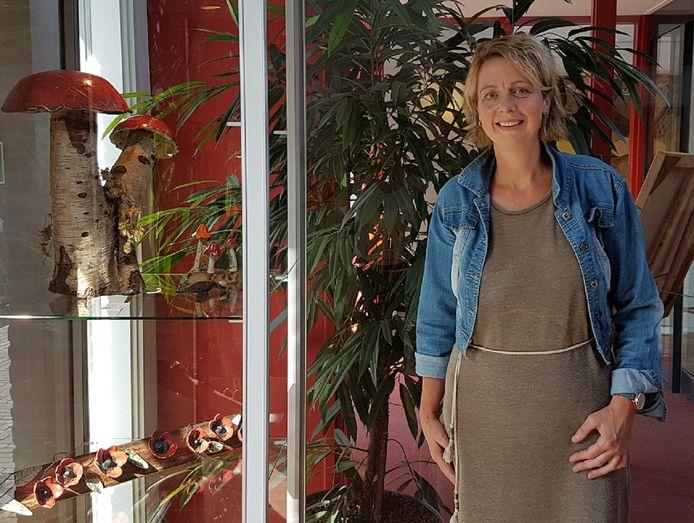 Denise Prinsen met een deel van haar werk bij een vitrine in De Huve.