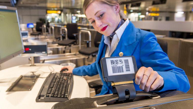 Een KLM-grondstewardess checkt een koffer in met het elektronische label van het Amsterdamse bedrijf Fast Track. Beeld anp